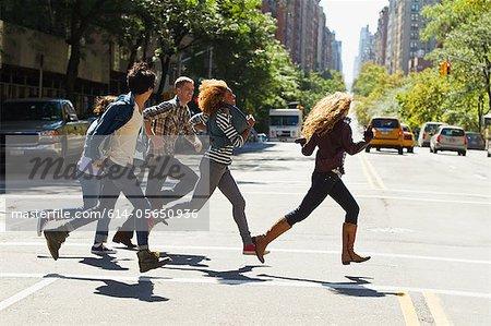 Five friends running through city street