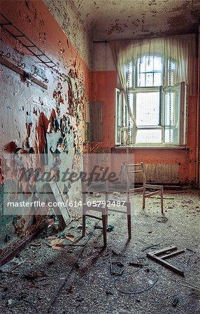 Broken chairs in decayed interior of Sanatorium Teupitz, Brandenburg, Germany