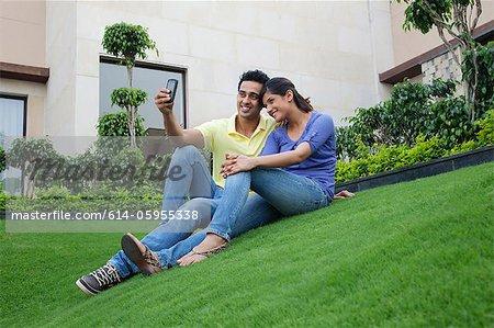 Couple taking a self portrait on a lawn