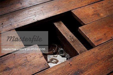 Money and jewellery under floorboards