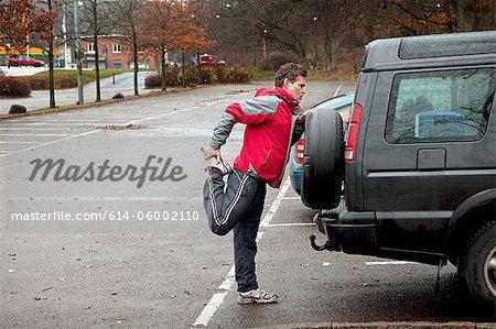 Mature man stretching against car in car park