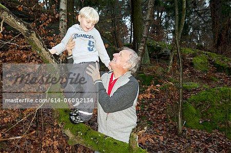 Grandfather holding boy on tree branch
