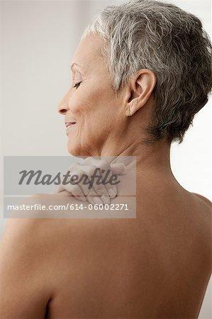 Senior woman massaging shoulder
