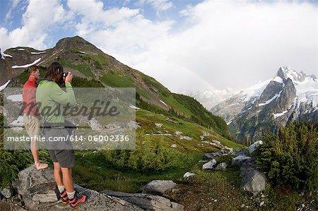 Photographing rainbow in mountains, White Rock Lakes, Ptarmigan Traverse, North Cascades, Washington, USA