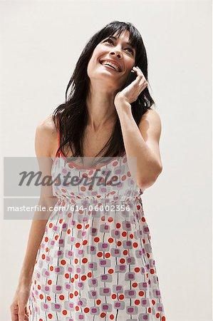 Smiling mature woman using cellphone, studio shot