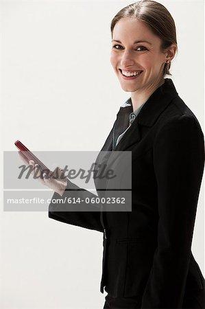 Portrait of young businesswoman using cellphone, studio shot