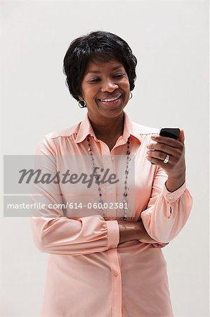 African American mature woman using cellphone, studio shot