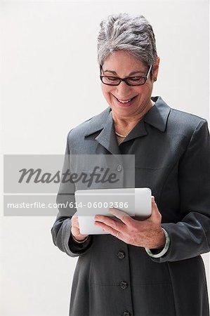 Mature businesswoman using digital tablet, studio shot
