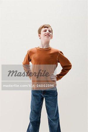 Boy in brown sweater in superhero stance, studio shot