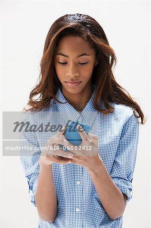 African American teenage girl using cellphone, studio shot