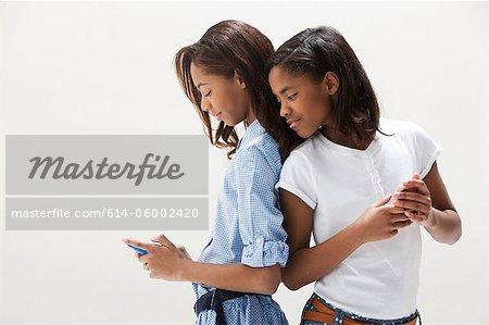 African American sisters using cellphones, studio shot