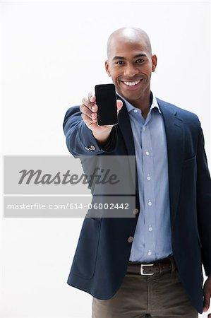 Portrait of African American man holding cellphone, studio shot