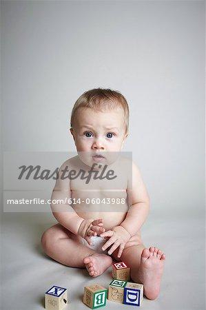 Baby boy with building blocks, looking surprised