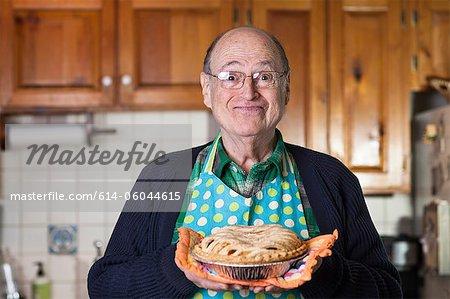 Senior man holding freshly baked pie, portrait