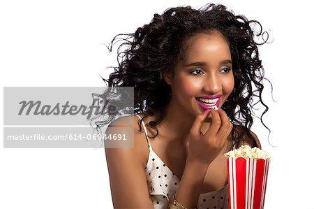 young woman eating popcorn studio shot stock photo masterfile