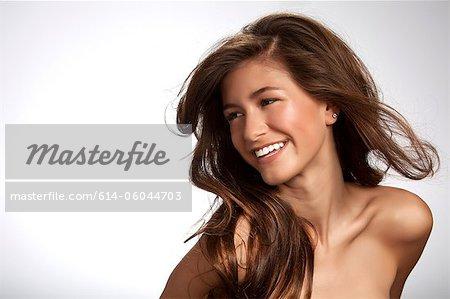 Teenage girl smiling against white background