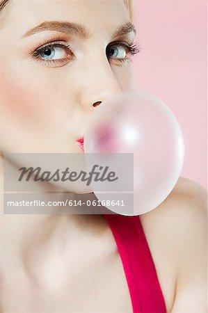 Young woman blowing bubblegum