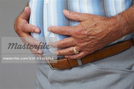 Overweight senior man touching stomach