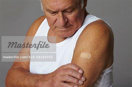 Senior man with plaster on arm