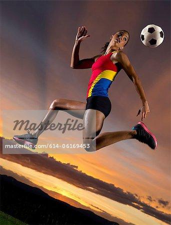 Female footballer in mid air against sunset