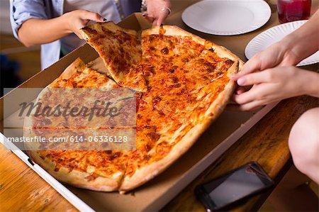 People sharing takeaway pizza