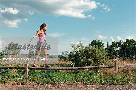 Teenage girl balancing on wooden fence