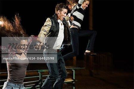Three friends jumping over bleachers at night