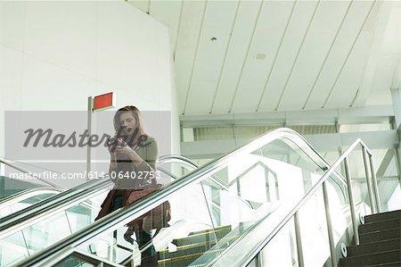 Young woman on escalator using smartphone