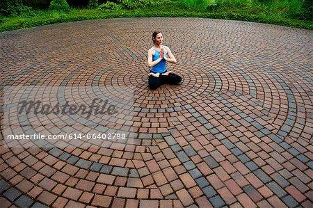 Woman meditating in paving stone circles