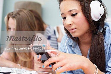 Teenage girl listening to music player
