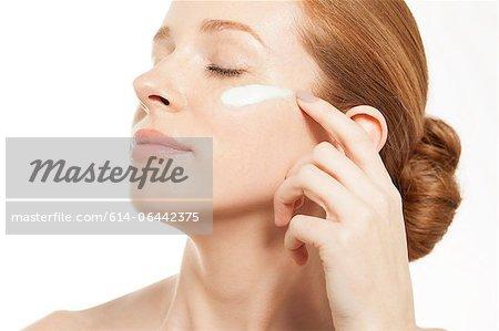 Woman applying moisturiser with eyes closed