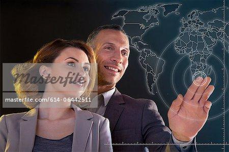Businesspeople touching world map