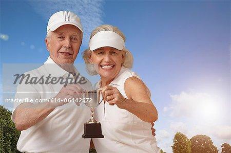 Senior couple holding tennis trophy