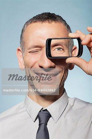 Man with smartphone over eye