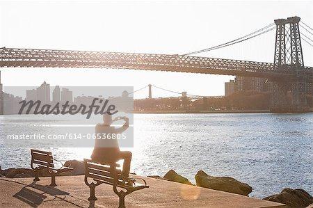 Man taking pictures of urban bridge