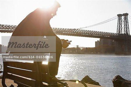 Man using cell phone by urban bridge