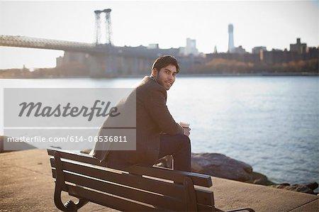 Smiling man sitting on park bench