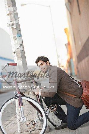 Man locking bicycle on city street
