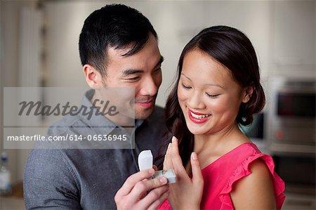 Man giving girlfriend engagement ring