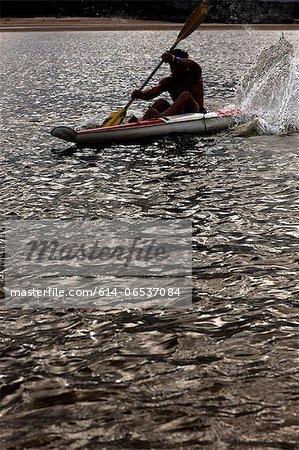 Man rowing kayak in lake