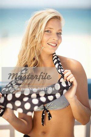 Woman in bikini playing with scarf