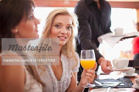 Woman having orange juice in cafe