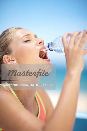 Woman drinking water bottle outdoors