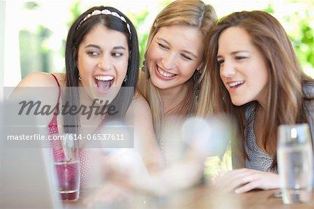 Smiling women using laptop together