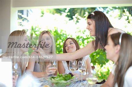 Woman feeding friend at table
