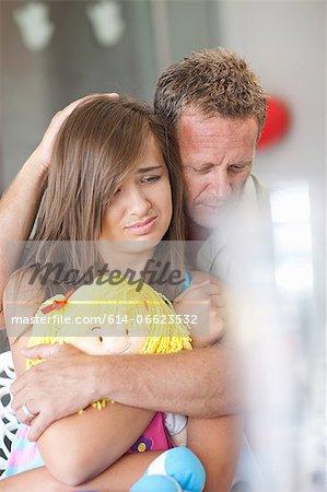 Father comforting teenage daughter