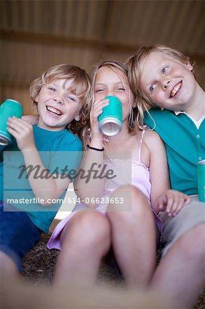 Children drinking soda in garage