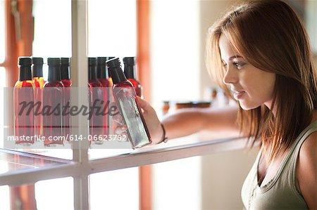 Woman reading vinegar bottle in grocery