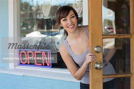 Woman peeking out front door of store