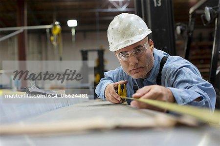 Worker measuring in metal plant